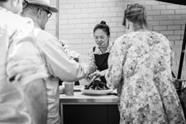 Corporate Event Photography | Melbourne Photography | Close up woman cooking and people watching black and white